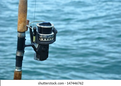 Close up of fishing reel in a fishing rod against sea