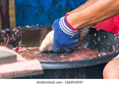 Close up of fishmonger's hands filleting fishes in a market at Thailand. A fishmonger killing and cutting fish.