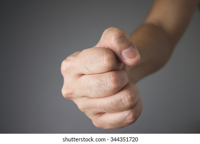 Close up fist on grey background.