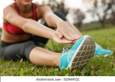 Close up of fit body of sport girl. She is sitting on green grass and doing exercising with concentration. The sportswoman is stretching her right leg and reaching for it with her arms