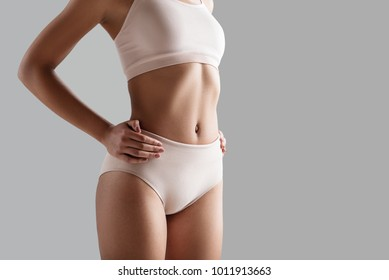 Close up of fit female body wearing tight panties and bra. She is holding hands on waistline. Copy space on right side. Isolated on background