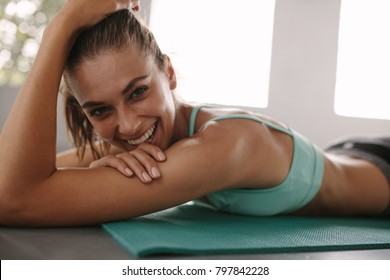 Close up of fit young female lying on exercise mat in gym and smiling. Healthy woman taking break after workout in gym.