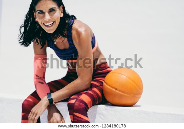 Close up of a fitness woman in cheerful mood sitting with a basketball by her side. Woman in fitness wear taking a break from workout and relaxing.