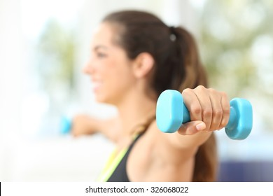 Close up of a fitness woman hand doing weights at home