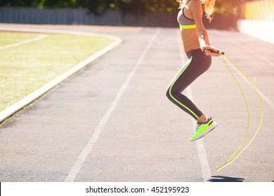 Close up of fitness-woman feet jumping, using skipping rope in stadium