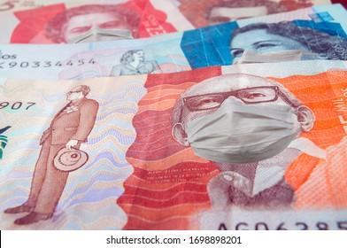 Cerca de un billete de cinco y veinte mil pesos colombianos con máscaras faciales que simbolizan el concepto de la crisis financiera en Colombia debido al coronavirus covid-19. Dinero colombiano
