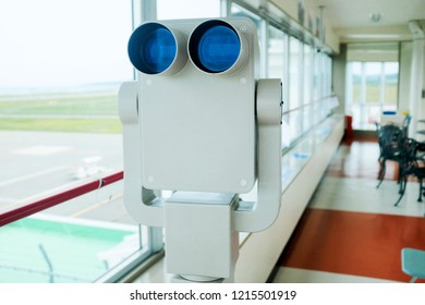 Close up of a fixed airport binoculars use for plane spotting inside a viewing deck