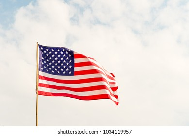 Close up Flag of United States of America (USA) waving in the wind with blue sky and cloudy