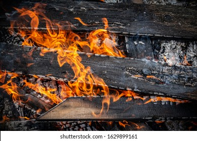A close up of flames of a burning wooden wall with charred vertical beams and horizontal charred boards