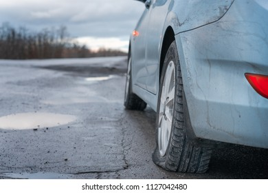 Close up Flat tire and blue car on the road after the rain waiting for repair