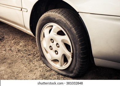 Close up Flat tire and old car on the road waiting for repair