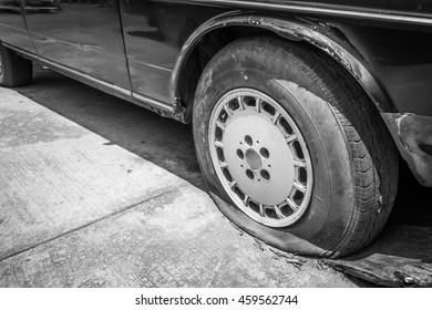 Close up Flat tire and old car on the road waiting for repair. Broken concept