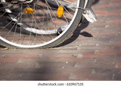 Close up flat tyres of parked bicycles in city.