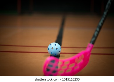 Close up of floorball stick and blue ball in the gym