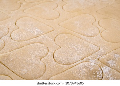 Close Up of Flour Dusted Heart Shaped Cookies in Dough