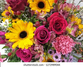 Close up of a flower bouquet which consists of carnations, roses, sunflowers and lilies