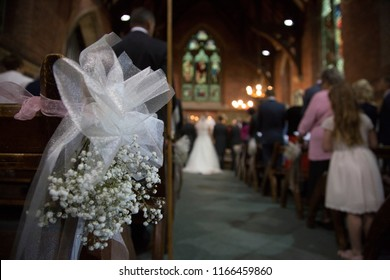 close up of flowers on the end of a pew in a church as the bride and groom stand at the alter saying their vows, bride and groom are soft focus and unrecognisable in the distance