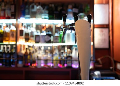 Close focus of beer tap in restaurant bar with shelves of alcohol defocused in the background