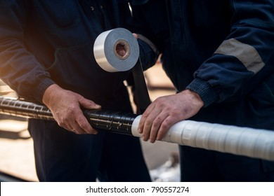 Close up focus hand view of professional industrial workers bonding meta pipe with duct tape.
