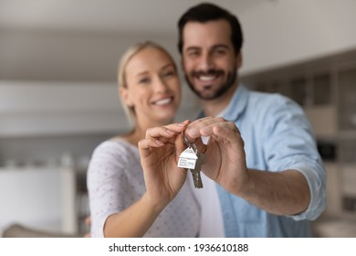 Close up focus of happy young Caucasian couple show keys to first share own apartment or house. Smiling millennial man and woman celebrate relocation to new home. Moving, rental, estate concept.