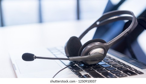 close up focus on call center headset device at telephone VOIP system at office desk for hotline telemarketing concept