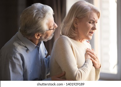 Close up focus on elderly wife hold hand on breast touch chest having heart attack feels unwell, worried husband supporting her, myocardial infarction symptoms, immediately emergency call need concept