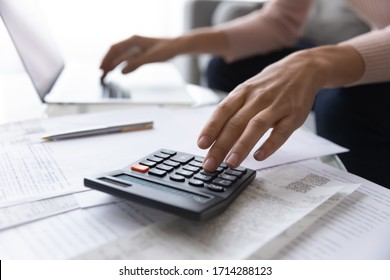 Close up focus on female hands making calculations. Young woman looking through paper bills, managing monthly household expenses and incomes, using e-banking application, planning investments.