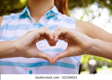 close up focus on gesture hands and fingers of  girl make love shape sign on her chest:anti and heal heart attack for healthy life,concept,instagram filter color