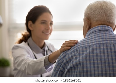 Close up focus on hand smiling female doctor touching old patient shoulder, comforting, good news, medical checkup results, physician therapist expressing empathy, psychological help concept