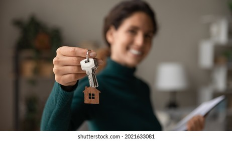 Close up focus on keys, smiling woman realtor selling apartment, offering to client, showing at camera, holding documents, contract, making purchasing deal, real estate agent, mortgage or rent