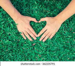 close up focus on man woman hand make heart shape of love sign on green grass background in vintage effect for take care of environment concept.