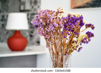 Close up focus on pretty purple violet bright colour flowers in glass vase inside of modern cozy living room or hotel accommodation, cute element at home, no people