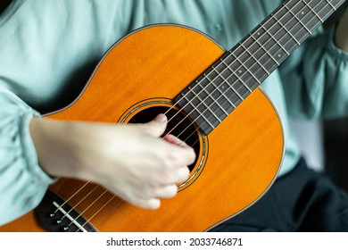 Close focus on strings and fingerboard of wooden solid spruce acoustic guitar strumming by blurry hand of woman.