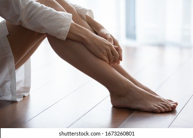 Close up focus on woman holding hands on legs. Unhappy young lady in nightgown bathrobe sitting alone on wooden floor, feeling desperate, thinking of personal problems, relations break up divorce.