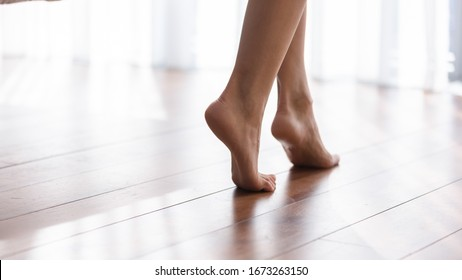 Close up focus on young female feet walking barefoot on clean wooden floor at home. Cropped image millennial woman girl standing on warm floor without slippers indoors, underfloor heating concept.