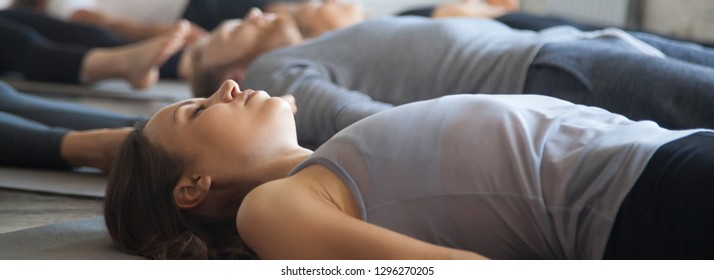 Close up focus on young woman practicing yoga lying in Savasana Corpse pose exercise at group training with girls guys in sport club wellness concept. Horizontal photo banner for website header design