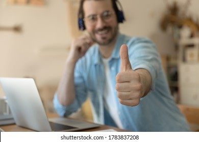 Close up focus of smiling young man client in headphones show thumb up give recommendation to online course, happy satisfied male customer recommend good quality distant training or education