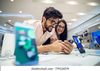 Close up focus view of a cheerful charming happy young student love couple choosing a new mobile in a tech store.