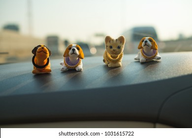 Close focus of waving dogs toy decoration on the car dashboard interior.