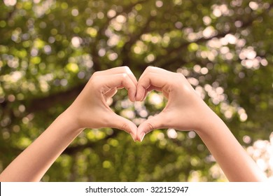close up focus woman hands gesture make heart on blurred natural tree forest background at outdoor park  for good living happy life concept.