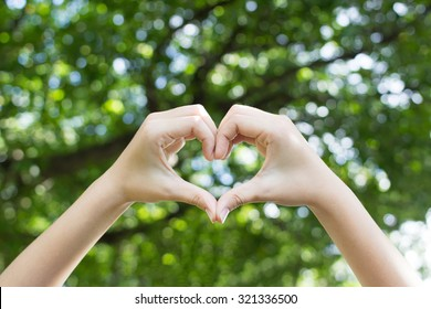 close up focus woman hands show love symbol on green nature outdoor park:heart shape:happy healthy life and avoid illness concept.
