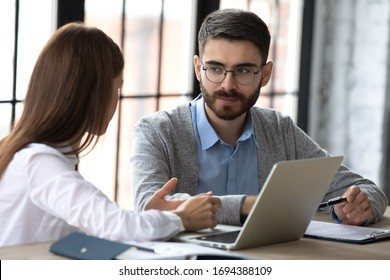 Close up focused businessman listening businesswoman talking in boardroom at meeting. Leader presenting new business concept for male colleague discuss. Team together using laptop for teamwork.