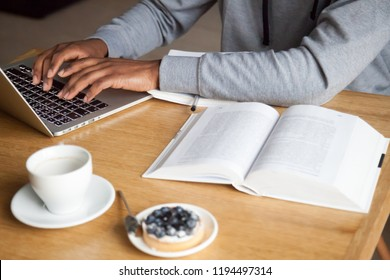 Close up of focused guy work at laptop typing on keyboard while sitting in café with books on table, man using computer studying in coffeeshop, enjoying coffee and dessert, male busy with gadget