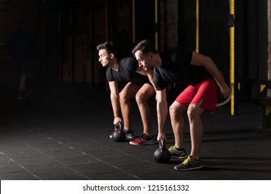 Close up of focused and motivated strong young fitness friends in sportswear crouching with the kettlebells reversed and doing squats in the gym.