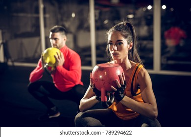 Close up of focused and motivated strong young fitness couple in sportswear crouching with the kettlebells reversed and doing squats in the gym.