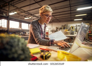 Close up of focused short hair attractive middle aged industrial female engineer with eyeglasses holding blueprints while working a laptop in the workshop.