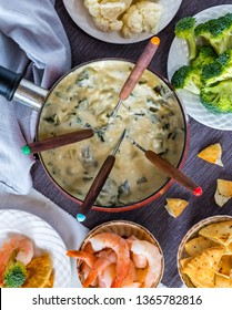 Close up of a fondue pot with spinach and artichoke cheese fondue surrounded by an assortment of food for dipping.