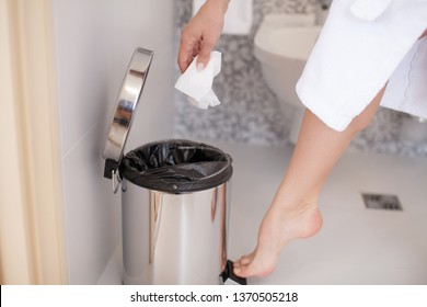 Close up of foot pressing a pedal to open cap of garbage bin. Young woman doing cleaning in the bathroom. Personal hygiene.