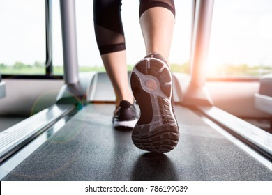 Close up foot sneakers Fitness girl running on track treadmill, Woman with muscular legs in exercise gym