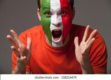 Close up of footbal fan. Italian footbal fan with painted face screamimg